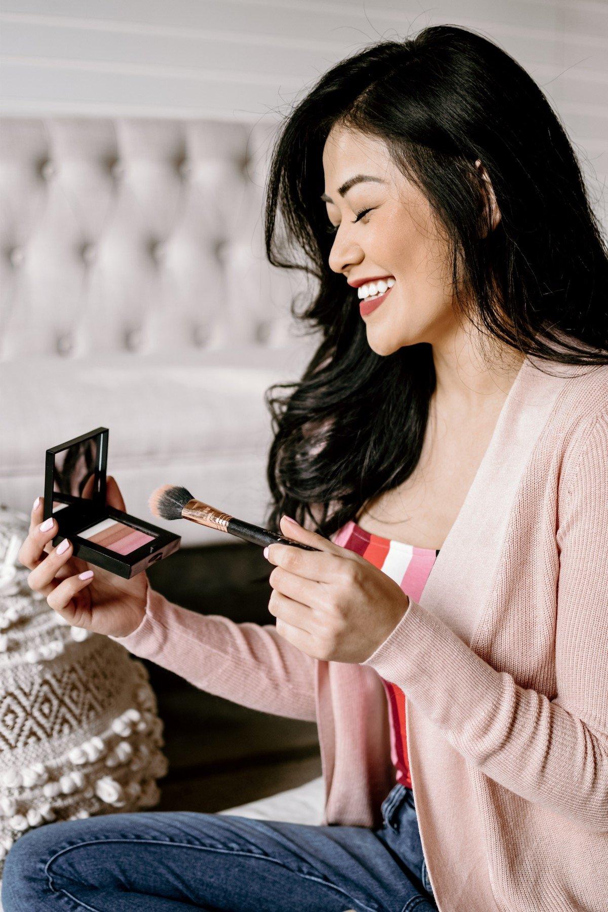 woman applying bobbi brown shimmer brick blush and smiling